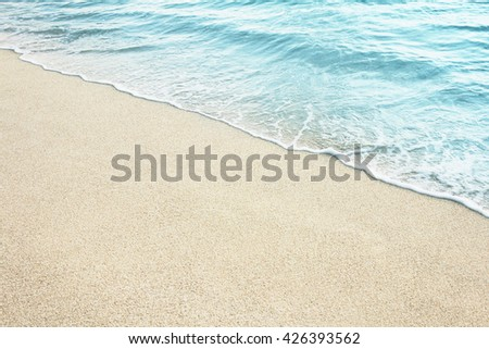 Soft Wave Of Blue Ocean On Sandy Beach. Background. Selective focus. - stock photo