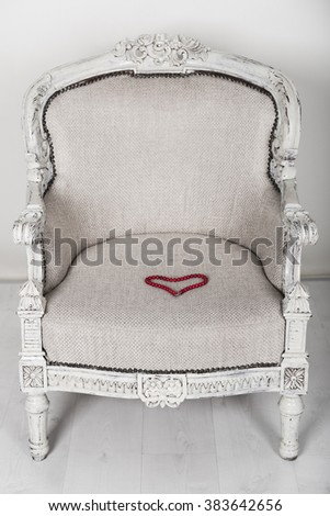 Soft white wooden chair in baroque style. On the chair is a red necklace in a shape of heart. - stock photo