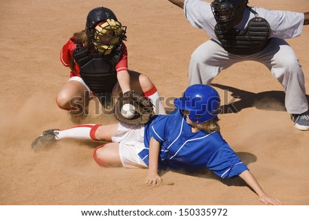 Softball player sliding into home plate while umpire rules safe - stock photo