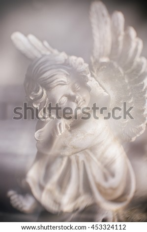 Softly blurred statue of an angel resting. - stock photo