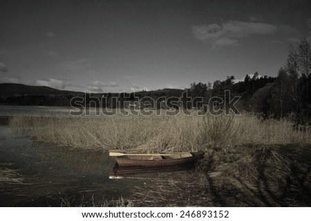 Softly textured image of rowboat on a lake a calm morning in sparse colors. - stock photo