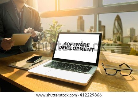 SOFTWARE DEVELOPMENT Thoughtful male person looking to the digital tablet screen, laptop screen,Silhouette and filter sun - stock photo