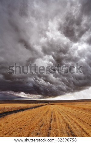 Soil rural road  to fields of Montana. The thunder-storm begins - stock photo