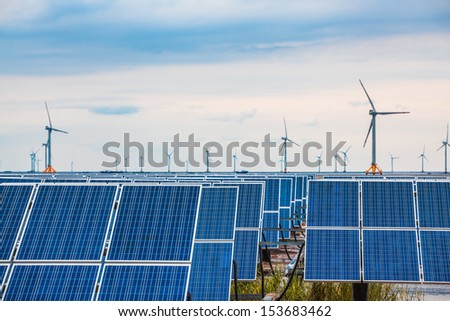 solar and wind power in coastal mud flat, clean energy complementary background. - stock photo