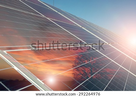Solar battery with reflection of orange sunset with tree on clear blue sky with highlight background, horizontal picture - stock photo