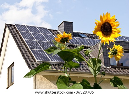 Solar cells on a roof with sun flowers in the foreground - stock photo