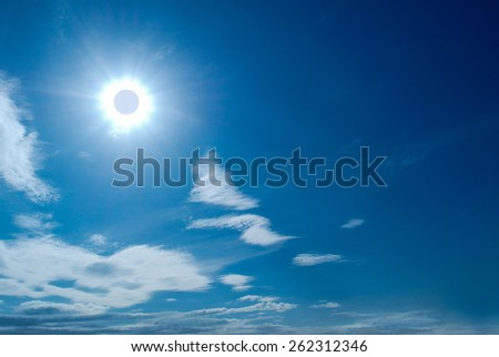 Solar Eclipse in blue sky among the clouds - stock photo