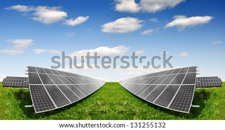 Solar energy panels against blue sky with clouds - stock photo