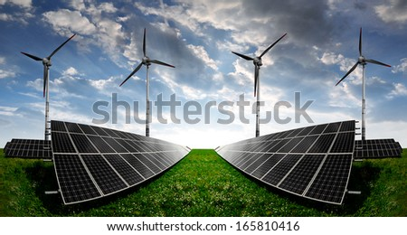 solar energy panels and wind turbines in the sunset - stock photo