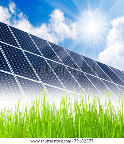 Solar energy panels in grass against sunny sky. - stock photo