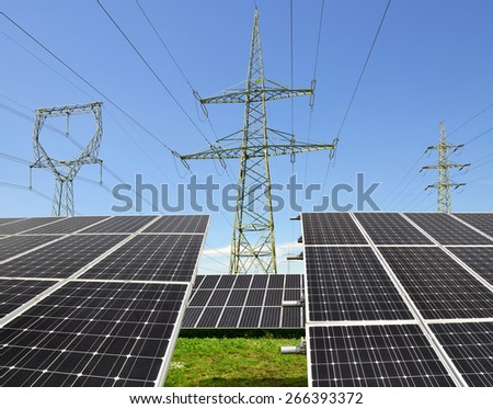 Solar energy panels with electricity pylons  - stock photo