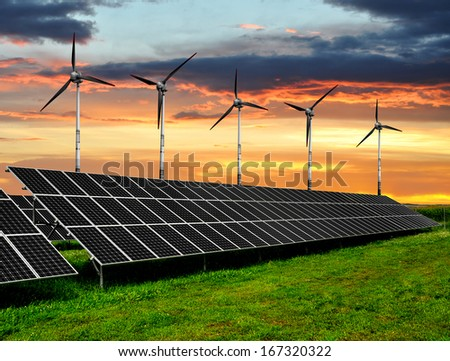 Solar energy panels with wind turbines in the setting sun  - stock photo