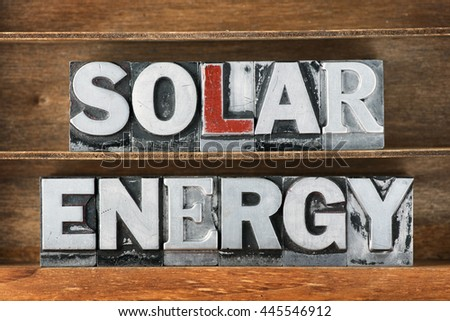 solar energy phrase made from metallic letterpress type on wooden tray - stock photo
