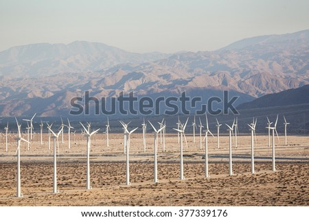 Solar Energy Windmills and Solar Panels in California Mountains in the background. Sunlight, solar panels and wind turbines. Environmental conservation and alternative power generation methods. - stock photo