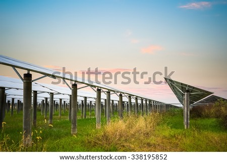 solar farm with sunset glow,  clean energy in autumn - stock photo