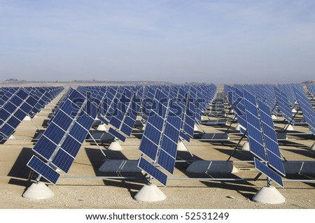 solar field with blue and cloudy sky - stock photo