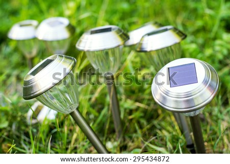 Solar garden lights are charged during the day in the sun - stock photo
