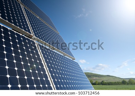 Solar Panel Against Blue Sky With Green Landscape - stock photo