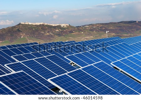 Solar panel installation with village in background in Molise (selective focus on panels) - stock photo
