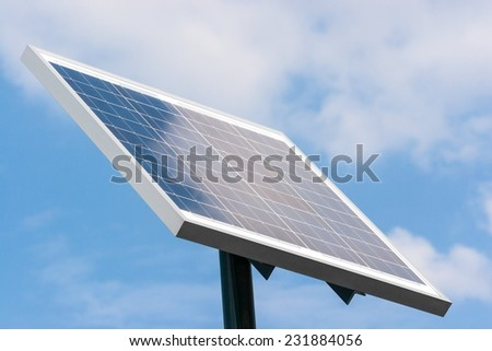Solar panel mounted on a pole towards right against blue sky and white clouds reflection.
