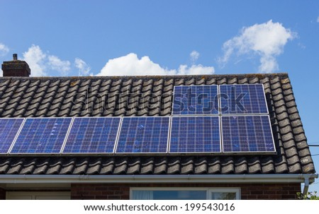 Solar panel on a  bungalow roof reflecting the sun. - stock photo