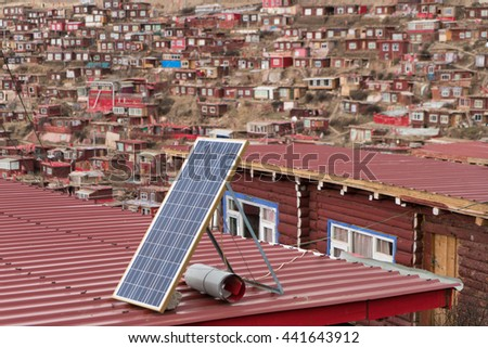 Solar panel on a red roof at Larung gar (Buddhist Academy) in Sichuan and blue sky background - stock photo