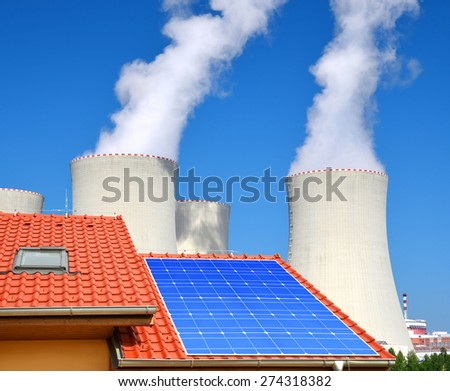Solar panel on the roof of the house in the background nuclear power plant. - stock photo