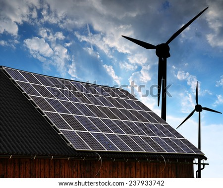Solar panel on the roof of the house in the background wind turbines at sunset.  - stock photo