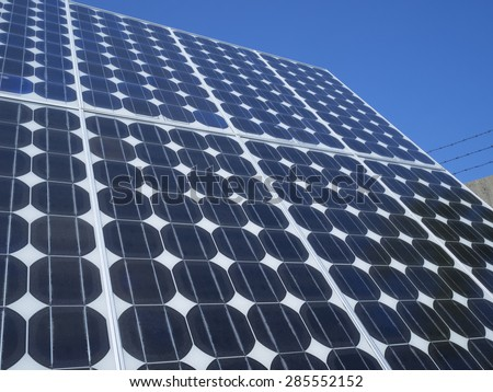 Solar panel photovoltaic cells array close up with cumulus clouds reflected in the panels. Solar energy is an ecofriendly power source which uses the sun to generate clean renewable energy. - stock photo
