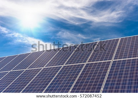 solar panel with strong sun and blue sky and clouds