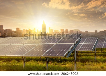 solar panels against city view on sunset - stock photo