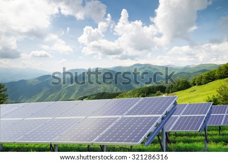 solar panels against mountain landscape against blue sky with clouds  - stock photo