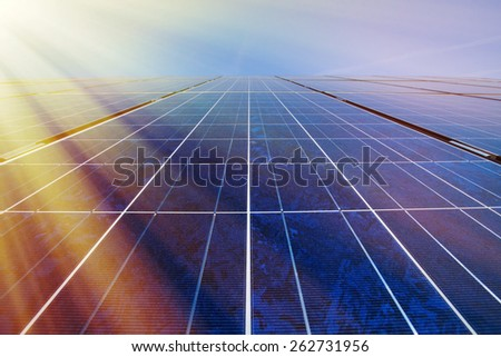 Solar panels and blue sky with sunlight shining on the panels - stock photo