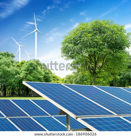 Solar panels and wind turbine against blue sky - stock photo