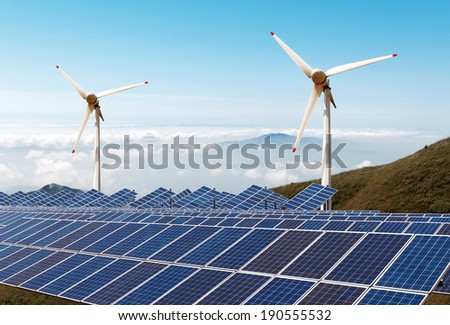 Solar panels and wind turbine against blue sky - stock photo