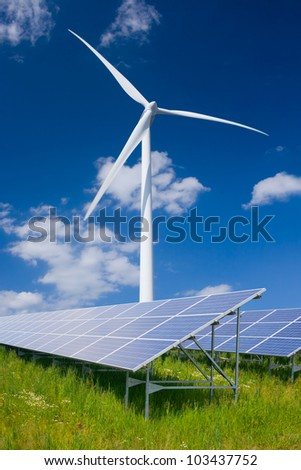 Solar panels and wind turbine against deep blue sky with clouds - stock photo