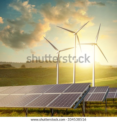 solar panels and wind turbines on sunset summer landscape - stock photo