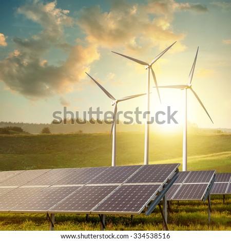 solar panels and wind turbines on sunset summer landscape - stock photo