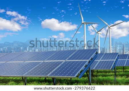 solar panels and wind turbines under blue sky and clouds with city on horizon - stock photo