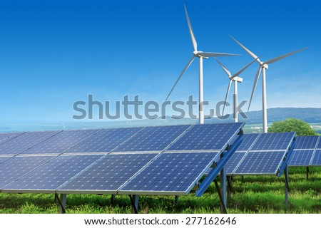 solar panels and wind turbines under blue sky on summer landscape - stock photo