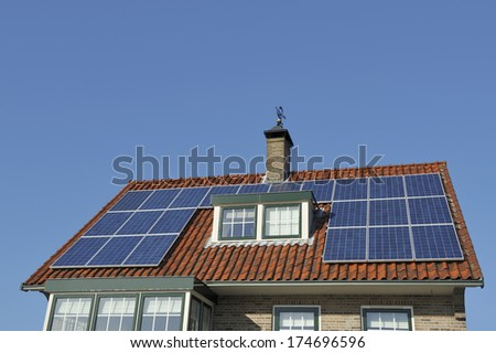 Solar Panels at red roof of old house. Copy space in clear blue sky. - stock photo