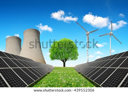 Solar panels before a nuclear power plant and wind turbines. Energy resources concept. - stock photo