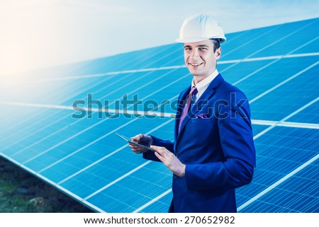 Solar panels. Engineer man with tablet on solar power station. - stock photo