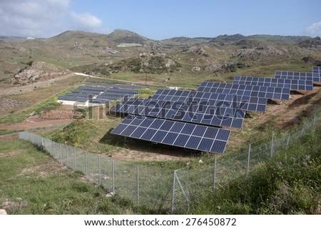 Solar panels in a field on hillside, Cyprus - stock photo