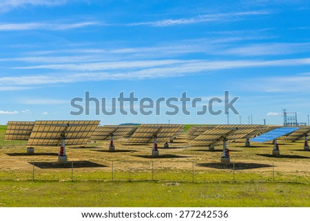 solar panels on a green field against the sky