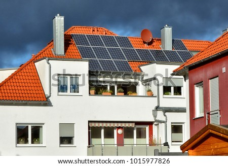 Solar panels on a red tile roof. Close up. Modern residential house. Alternative energy. German accommodation.