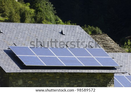 solar panels on a roof of stone slate - stock photo