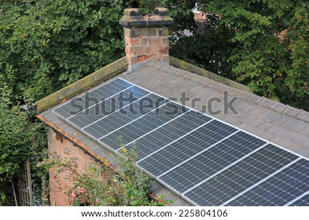 Solar panels on an old house showing the desire for sustainable energy and mixing old with new - stock photo