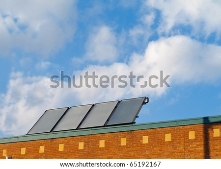 Solar panels on roof of small commercial building - stock photo