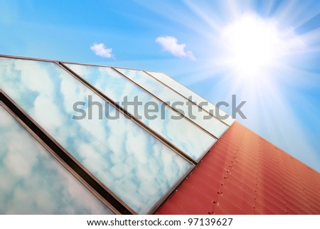 Solar panels on the red house roof with blue sky, sun and clouds - stock photo